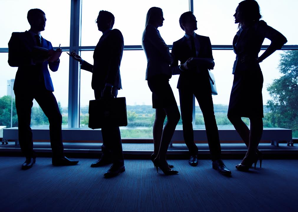 Group of employees having business meeting against window